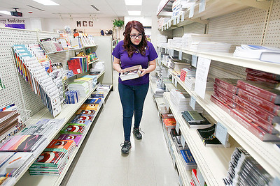 Sarah Nader- snader@shawmedia.com Kristal Nance, 20, of McHenry stocks a book on the shelf while working at the McHenry County College book store in Crystal Lake Thursday, March 6, 2014. Nance has been part of the Work Study program at the college since last August.