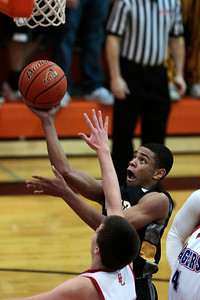 Kyle Grillot - kgrillot@shawmedia.com   Jacobs junior Kenton Mack (right) puts up a shot under pressure from Dundee-Crown senior Connor Steinmetz during the third quarter of the Class 4A Crystal Lake Central Regional final Friday, March 7, 2014. Jacobs beat Dundee-Crown, 43-33.