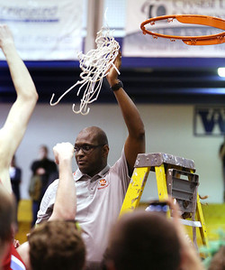 John Konstantaras - For Shaw Media Marian Central head coach Curtis Price holds up one of the nets after winning their Class 3A regional final game against Marengo at Woodstock High School Friday March 7, 2014 Woodstock.  The Hurricanes won the game 72-53.