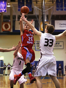 John Konstantaras - For Shaw Media Marian Central's Wyatt Lindell (20) drives on Marengo's Adam Rogutich (33) during the fourth quarter of their Class 3A regional final game at Woodstock High School Friday March 7, 2014 Woodstock.  The Hurricanes won the game 72-53.