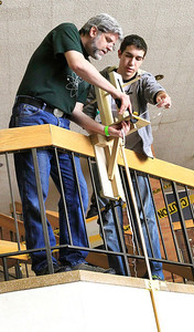 Candace H. Johnson - For Shaw Media Grayslake Central's Dan Cahill works with Huntley senior Zach Ott, 18, as he demonstrates his Bungee Drop experiment during the College of Lake County's Regional Science Olympiad Competition in Grayslake.