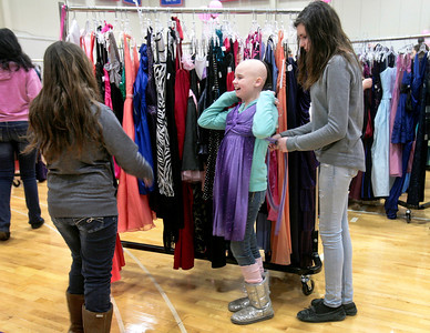"Michelle LaVigne/ For Shaw Media Kate Duh, 10, of McHenry, laughs as her sister Jackelyn Duh, 13, has her ""model"" a prom dress. Jackelyn Duh was shopping at the Big Brother's Big Sister's ""My Sister's Dress"" prom dress event at McHenry County College in Crystal Lake on Sunday, March 5th, 2014 for her eighth grade dance."