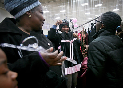 "Michelle LaVigne/ For Shaw Media While her mother Cynthia Myrie of Wheeling, left, holds a dress, and her sister Kameal Myrie, 6, watches the shopping process, Denorsia Baptist,18, right, checks out the dress being shown by her aunt Andrea Rose of Des Plaines, while shopping at the Big Brother's Big Sister's ""My Sister's Dress"" prom dress sales event at McHenry County College in Crystal Lake on Sunday, March 5th, 2014."