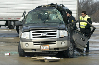 Police investigators check the interior of an SUV folowing an accident at Kreutzer Road and Route 47 in Huntley.  H. Rick Bamman - hbamman@shawmedia.com