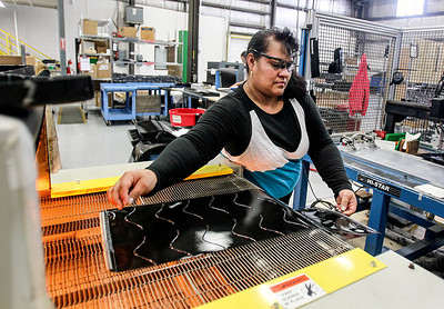 Sarah Nader- snader@shawmedia.com Margarita Hernandez process bun toaster belts  while working at Advanced Flexible Composites in Lake in the Hills Thursday, March 13, 2014. The family-owned business has seen double-digit growth and increased shifts along with being named a McHenry County Economic Development Corp. 2013 Business Champion.