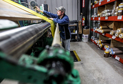 Sarah Nader- snader@shawmedia.com Converter Tim Nachtwey works on a roll off machine while working at Advanced Flexible Composites in Lake in the Hills Thursday, March 13, 2014. The family-owned business has seen double-digit growth and increased shifts along with being named a McHenry County Economic Development Corp. 2013 Business Champion.