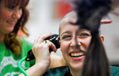 Kyle Grillot - kgrillot@shawmedia.com   Marian Central sophomore Nora Tucker, 16, reacts as a friend holds a lock of her hair while she has her head shaved participating in the McHenry Community Shave for St. Baldrick's Day in McHenry Thursday, March 13, 2014. Over the past five years, McHenry East and West staff, students, and community members have had over 1900 heads shaved and raised over $489,000 for the St. Baldrick's Foundation.