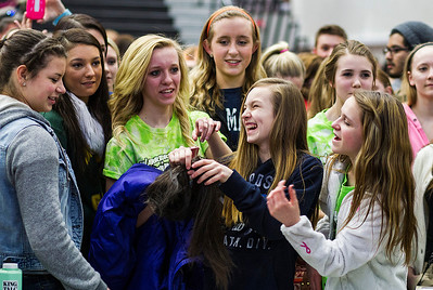 Kyle Grillot - kgrillot@shawmedia.com   Spectators hold a lock of hair from Nora Tucker, 16, after having her head shaved participating in the McHenry Community Shave for St. Baldrick's Day in McHenry Thursday, March 13, 2014. Over the past five years, McHenry East and West staff, students, and community members have had over 1900 heads shaved and raised over $489,000 for the St. Baldrick's Foundation.