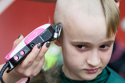 Kyle Grillot - kgrillot@shawmedia.com   Ethan O'Rourke, 10, of McHenry reacts as he has his head shaved participating in the McHenry Community Shave for St. Baldrick's Day in McHenry Thursday, March 13, 2014. O'Rourke raised $435 dollars for the event. Over the past five years, McHenry East and West staff, students, and community members have had over 1900 heads shaved and raised over $489,000 for the St. Baldrick's Foundation.