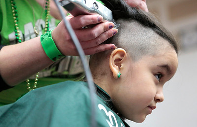 Kyle Grillot - kgrillot@shawmedia.com   Valentina Luqueno, 6, of McHenry looks to her parents as she begins to have her head shaved participating in the McHenry Community Shave for St. Baldrick's Day in McHenry Thursday, March 13, 2014. Over the past five years, McHenry East and West staff, students, and community members have had over 1900 heads shaved and raised over $489,000 for the St. Baldrick's Foundation.