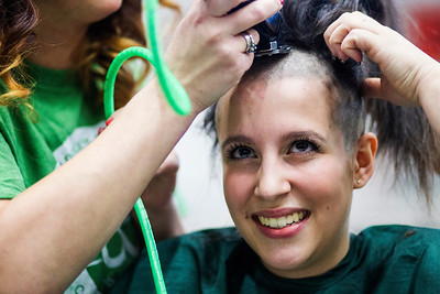 Kyle Grillot - kgrillot@shawmedia.com   Marian Central sophomore Nora Tucker, 16, looks to her friends as she begins to have her head shaved participating in the McHenry Community Shave for St. Baldrick's Day in McHenry Thursday, March 13, 2014. Over the past five years, McHenry East and West staff, students, and community members have had over 1900  heads shaved and raised over $489,000 for the St. Baldrick's Foundation.