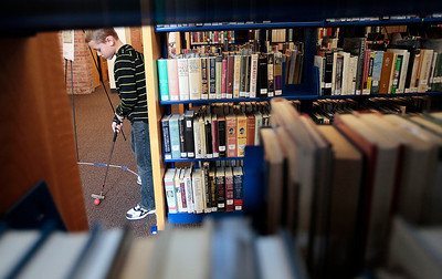 "Kyle Grillot - kgrillot@shawmedia.com   Grant Stinger, 8, of Huntley putts in between bookshelves Saturday at the Woodstock Library. The 18 hole golf course weaves through the library and is open to golfers of all ages. Regional golf course professionals played the course early Saturday, and each player has the chance to win prizes and ""beat the pros."""
