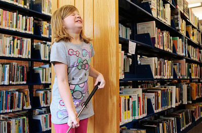 "Kyle Grillot - kgrillot@shawmedia.com   Madalyn Sloan, 7, of Lake in the Hills reacts after missing a hole-in-one chance to win a prize Saturday at the Woodstock Library. The 18 hole golf course weaves through the library and is open to golfers of all ages. Regional golf course professionals played the course early Saturday, and each player has the chance to win prizes and ""beat the pros."""