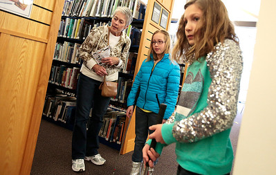 "Kyle Grillot - kgrillot@shawmedia.com   Elaine Stinger, of Wonder Lake (left) watches as her granddaughters Carly Stinger, 9, (center) and Lauren Bauer, 10,  as they putt in between bookshelves Saturday at the Woodstock Library. The 18 hole golf course weaves through the library and is open to golfers of all ages. Regional golf course professionals played the course early Saturday, and each player has the chance to win prizes and ""beat the pros."""