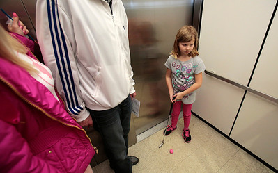 "Kyle Grillot - kgrillot@shawmedia.com   Madalyn Sloan, 7, of Lake in the Hills waits to putt out of an elevator Saturday at the Woodstock Library. The 18 hole golf course weaves through the library and is open to golfers of all ages. Regional golf course professionals played the course early Saturday, and each player has the chance to win prizes and ""beat the pros."""