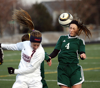 Joseph Cyganowski - For Shaw Media Leah Celarek, left, and Erin Woeste, right, got to the air. The Gators of Crystal Lake South High School, opened the soccer season,  travelling to Conant High School in Hoffman Estates to  battle the Cougars,  Monday, March 17, 2014.