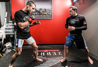 Sarah Nader- snader@shawmedia.com Pat Curran (left), who trains in Crystal Lake, warms up with his coach, Jeff Curran, in his dressing room before fighting Daniel Straus of Cincinnati during the Bellator MMA 112 featherweight world title bout Friday, March 14, 2014 at Horseshoe Casino in Hammond, Ind. Curran won the fight.
