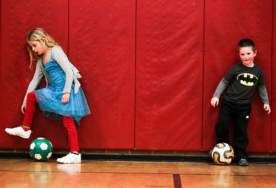 Sarah Nader- snader@shawmedia.com Chloe Franklin (left), 6, of McHenry and Aidan Mueller, 4, of McHenry dribble around the gym while attending a McHenry Park and Recreation soccer camp at Chauncey Duker School in McHenry Tuesday, March 18, 2014. To keep kids active and having fun over spring break, the McHenry Parks and Recreation Department is offering a five-day camp. The camp is for children in first through fifth grades and runs from 9 a.m. to 3 p.m. starting Monday.