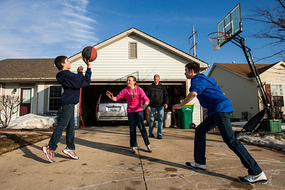 """Kyle Grillot - kgrillot@shawmedia.com   Sean Murrin (second from right) takes advantage of warm weather to teach, and play basketball with his kids Nathan, 12, (right) Sydney, 11, (center) as well as their friend Aidan Weyland, 13, outside Murrin's McHenry home Tuesday, March 18, 2014. """"I can't remember any other year where we're had snow from November to March,"""" said Murrin. A mixture of snow and rain is expected through Wednesday, yet highs near 50 degrees are expected to return later in the week."""