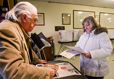 Sarah Nader- snader@shawmedia.com Volunteer Len Klosowicz (left) of McHenry helps Dee Hess of McHenry hand in her ballet after she voted at the American Legion Tuesday, March 18, 2014.