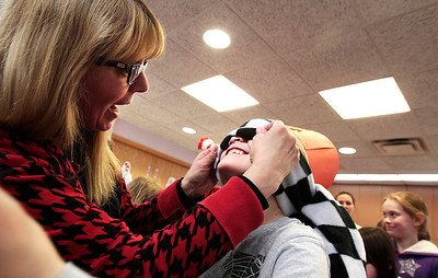 Kyle Grillot - kgrillot@shawmedia.com   Youth Services Manager Carol Dolan helps Ben Klein, 8, of Fox River Grove with a blind fold before pinning green eggs to the ham during Dr. Seuss' 110th Birthday celebration Thursday at the Fox River Grove Memorial Library.