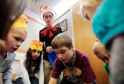 Kyle Grillot - kgrillot@shawmedia.com   Library Page Michael Elliot watches over children including Ben Klein, 8, (from left) Maddy Patlan, 9, Noah Marrano, 8, and Grant Bond, 7, as they work together on a puzzle during Dr. Seuss' 110th Birthday celebration Thursday at the Fox River Grove Memorial Library.