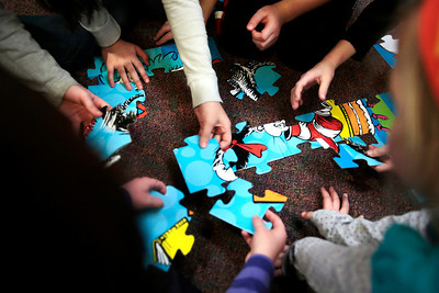 Kyle Grillot - kgrillot@shawmedia.com   Children work together on a puzzle during Dr. Seuss' 110th Birthday celebration Thursday at the Fox River Grove Memorial Library.