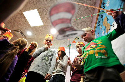 Kyle Grillot - kgrillot@shawmedia.com   Youth Services Manager Carol Dolan (left) watches as Ben Klein, 8, (from left) Maddy Patlan, 9, Noah Marrano, 8, and Grant Bond, 7, fish for Dr. Seuss pictures during Dr. Seuss' 110th Birthday celebration Thursday at the Fox River Grove Memorial Library.