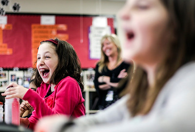 "Sarah Nader- snader@shawmedia.com Fourth-grade students, Annaliese Harper (left), 10 and Maggie Becker, 9, both of Lake in the Hills, laugh while guest reader, Ryan Kunde reads, ""Are You My Mother?"" to the fourth-grade class at Martin Elementary in Lake in the Hills Thursday, March 20, 2014. The school set a new record by utilizing over 80 guest readers throughout the day during Reading Week at the school."