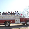 Mooseheart basketball players ride on a fire truck on the school's campus following a celebration that honored the school's athletes Friday morning. Mooseheart won the IHSA Class 1A state basketball title last weekend.