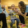 Max Slowiek, age 3, from Elburn, gets his face painted by 13-year-old volunteer Megan Clark, from Batavia, during the Buddy Break monthly event at First Batavia Church March 22.