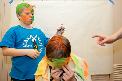 Michelle LaVigne/ For Shaw Media Ten-year-old Roy Money of Lake-in-the-Hills adds a final coat of colored hair spray to his 12-year-old brother Stuart Money during the Shamrock Shave Charity Fundraiser at St. Margaret Mary School in Algonquin on Saturday, March 14, 2015.