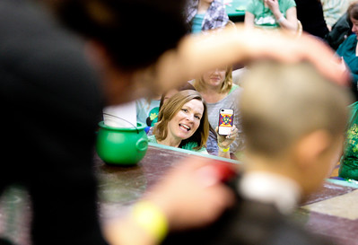 Michelle LaVigne/ For Shaw Media Sandy Manaois takes video of her 10-year-old son Sam as he gets his head shaved in the first round of participants in the Shamrock Shave Charity Fundraiser at St. Margaret Mary School in Algonquin on Saturday, March 14, 2015.