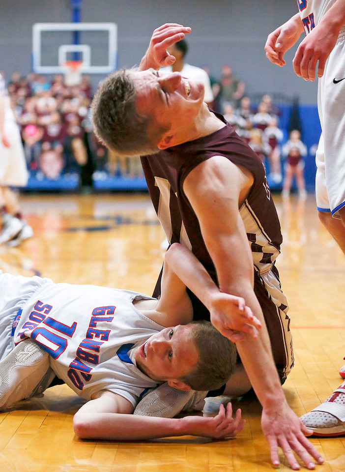 Michael Volkening (11) from Marengo leans back as Ethan Sowl (10) from Glenbard South falls on his ankles as they scramble for a rebound during the fourth quarter of their Class 3A sectional game at Genoa-Kingston High School Wednesday, March 8, 2017 in Genoa. The Indians defeated the Raiders 50-49. John Konstantaras photo for the Northwest Herald