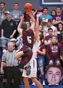 Blaine Borhart (5) from Marengo scores a basket over Charlie Bair (50) from Glenbard South during the third quarter of their Class 3A sectional game at Genoa-Kingston High School Wednesday, March 8, 2017 in Genoa. The Indians defeated the Raiders 50-49. John Konstantaras photo for the Northwest Herald