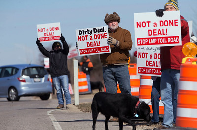 Chris Salem, center, from Dundee Township, holds a sign along Randall Rd as over 50 concerned citizens came out to protest the expansion of Longmeadow Parkway and toll bridge on Saturday, March 11, 2017 in Algonquin, Ill.  John Konstantaras photo for the Northwest Herald