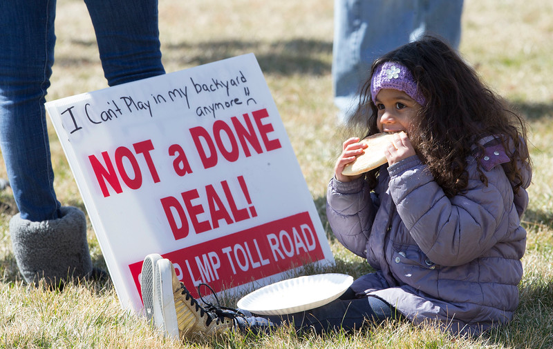 Ariana Williams, 3, eats apiece of pizza while taking a break from protesting with her mom Lindsay along Longmeadow Parkway on Saturday, March 11, 2017 in Algonquin, Ill. Over 50 concerned citizens protest to stop the expansion of Longmeadow Parkway and toll bridge  John Konstantaras photo for the Northwest Herald