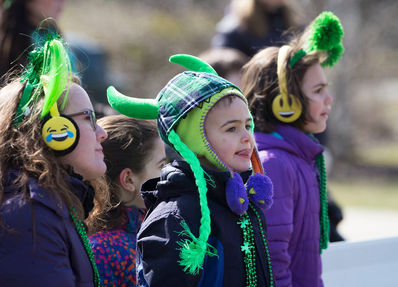 Logan Beyer, center, 6 from McHenry, watches dancers perform at Veteran's Park with his mother Elizabeth and sisters Reagan and Morgan after the St. Patrick's Day parade on Sunday, March 12, 2017 in McHenry. The Beyer family was in the parade with St. Patrick's church.  John Konstantaras photo for the Northwest Herald