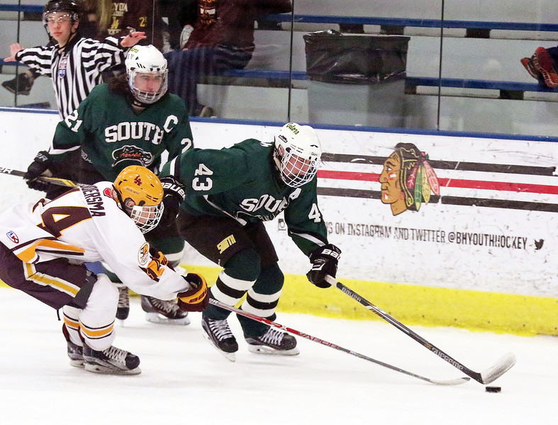Crystal Lake South's Eric Helm is defended by Loyola Academy's Owen Boersma during Friday's Blackhawk Cup White State Tournament championship at the Edge Ice Arena in Bensenville. The Gators lost 6-1.