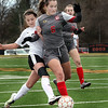 Batavia's Anna Rakos and Wheaton-Warrenville South's Ellery Fahey battle for the ball during a game in Wheaton March 18.