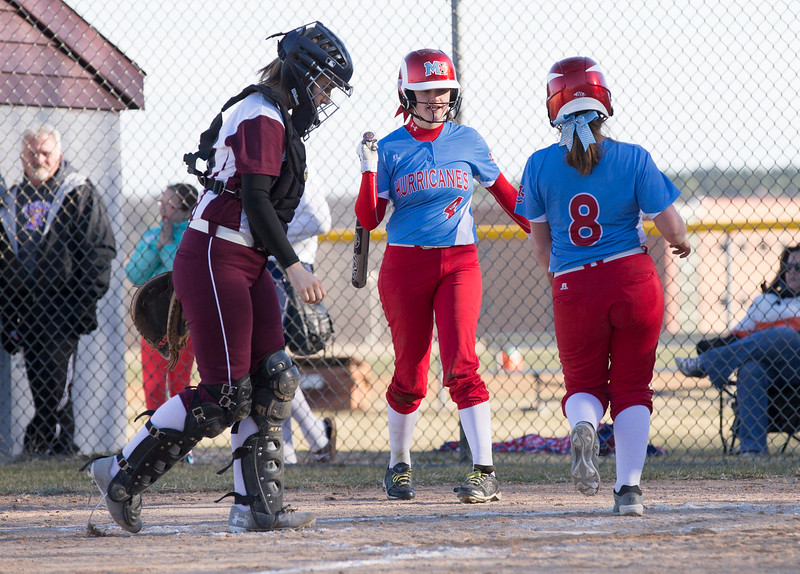 John Konstantaras - For the Northwest Herald  Prairie Ridge's catcher Ashleigh Dierking (28) walks to the plate as Marian Central's Kaeti Miller (8) is greeted by Emily Miller (4) as she scores during their game at Prairie Ridge High School  on Tuesday, March 21, 2017 Crystal Lake.