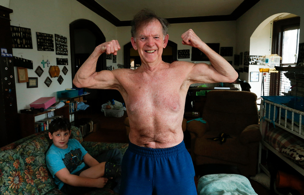 "John Konstantaras - For Shaw Media ""Crazy Patrick"" Howden, 73, shows his muscles after setting a record of 5,800 reps with 8-pound weights in his home on Sunday, March 26, 23017 in Harvard."