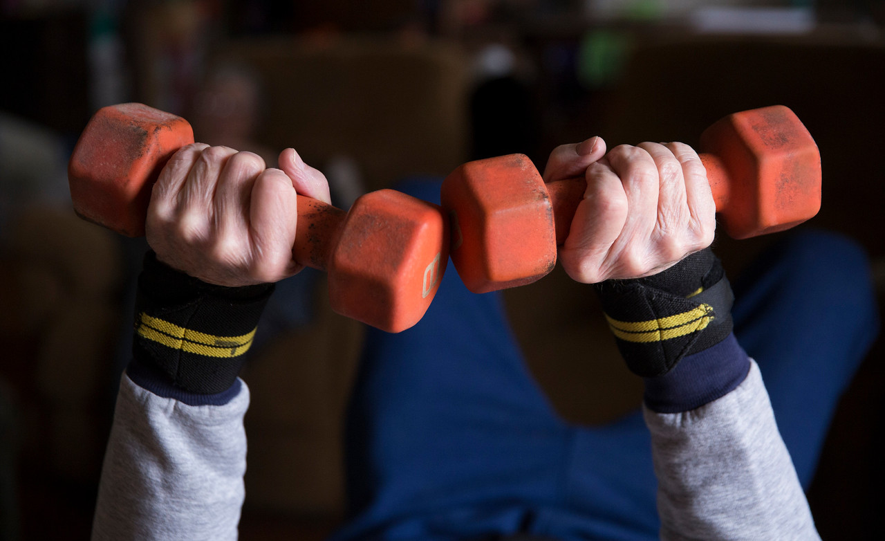 """John Konstantaras - For Shaw Media""""Crazy Patrick"""" Howden, 73, takes a short break as he sets a record doing 5,800 reps with 8-pound weights in his home on Sunday, March 26, 23017 in Harvard."""