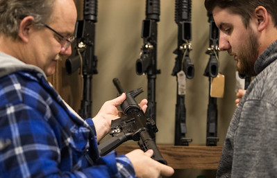 Whitney Rupp for Shaw Media Tim Davis, along with his son Tim Davis, both of McHenry, inspect a rifle while shopping at Second Amendment Sports in McHenry Friday, March 2. **Ed. Note: Photographer asked and subjects depicted are not Sr. and Jr.**