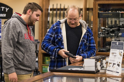 Whitney Rupp for Shaw Media Tim Davis, along with his son Tim Davis, both of McHenry, inspect a handgun while shopping at Second Amendment Sports in McHenry Friday, March 2.  **Ed. Note: Photographer asked and subjects depicted are not Sr. and Jr.**