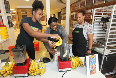 Candace H. Johnson-For Shaw Media Norsha Watts (on right) watches over her daughter, Tiesha, 15, and niece, Jeanett Taylor, 17, all of Chicago as they make a fruit smoothie in their Maui Wowi booth during the Business & Craft Expo at Grant Community High School in Fox Lake. The event was sponsored by the Fox Lake Area Chamber of Commerce & Industry.(3/3/18)