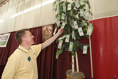 Candace H. Johnson-For Shaw Media James Norris, of Wauconda, financial advisor with Edward Jones Investments shows the money tree he was raffling off during the Business & Craft Expo at Grant Community High School in Fox Lake. The event was sponsored by the Fox Lake Area Chamber of Commerce & Industry.(3/3/18)