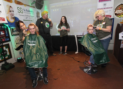 "Candace H. Johnson-For Shaw Media Darren Gorman, 14, of Round Lake and his brother, Aidan, 10, get their heads shaved as Tom Welninski, of Antioch, organizer, and his daughter, Anne, 18, of Lakemoor talk to the crowd during Kristof's Cares 4 Kids, ""Rock the Bald,"" St. Baldrick's event at Kristof's Entertainment Center in Round Lake Beach. The brothers were getting their heads shaved in honor of their father, Jason, who is in remission from non-Hodgkin's lymphoma."
