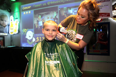 "Candace H. Johnson-For Shaw Media Jason Melton, 7, of Ingleside gets his head shaved by Nicole Nelson, of Twin Lakes, Wis., during Kristof's Cares 4 Kids, ""Rock the Bald,"" St. Baldrick's event at Kristof's Entertainment Center in Round Lake Beach. Jason had his head shaved in honor of his cousin, Nik."