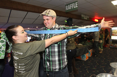 "Candace H. Johnson-For Shaw Media Volunteer Kaye Jonescue, of LaCrosse, Wis., measures an arms length of raffle tickets on Peter Rinkema, of Spring Grove during Kristof's Cares 4 Kids, ""Rock the Bald,"" St. Baldrick's fundraising event at Kristof's Entertainment Center in Round Lake Beach."